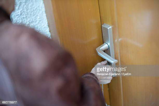 Midsection Of Person Opening Door With Keys