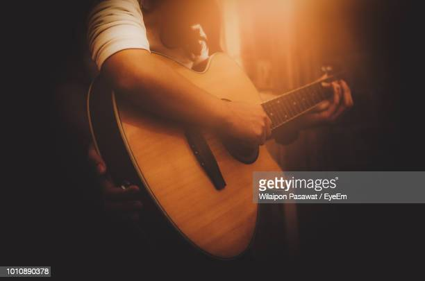 midsection of person playing guitar - acoustic guitar stock pictures, royalty-free photos & images