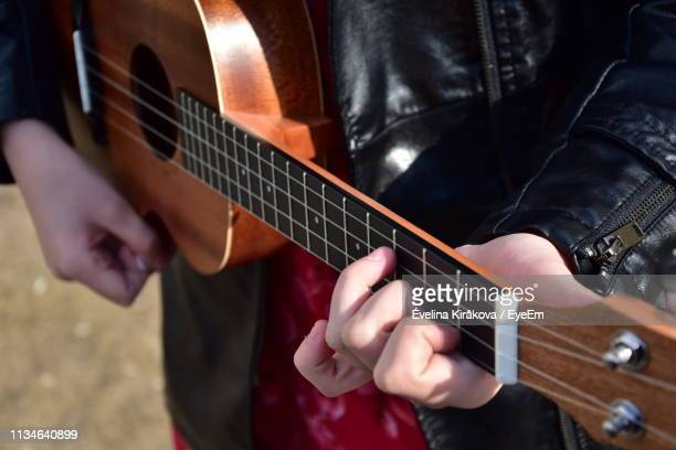 midsection of person playing guitar - modern rock stock pictures, royalty-free photos & images