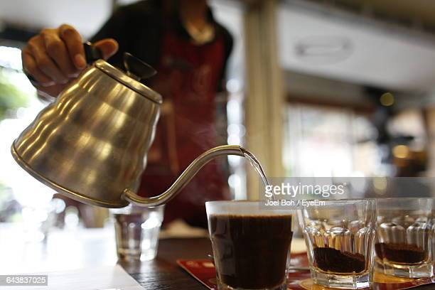 Midsection Of Person Pouring Hot Water In Coffee Cup At Shop