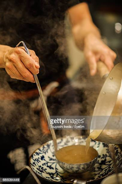 midsection of person pouring soup in ladle - ladle stock photos and pictures