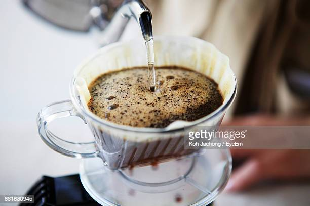 Midsection Of Person Pouring Water In Coffee