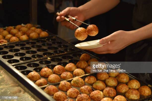 midsection of person preparing food on barbecue grill - takoyaki stock pictures, royalty-free photos & images