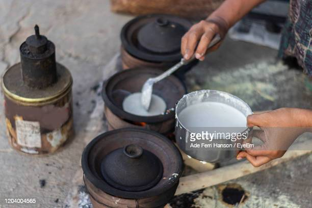 midsection of person preparing food on barbecue grill - grillade stockfoto's en -beelden