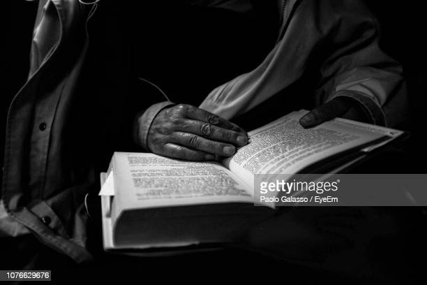 midsection of person reading book in darkroom - literature stock pictures, royalty-free photos & images