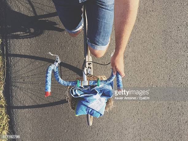 Midsection Of Person Riding Bicycle On Street