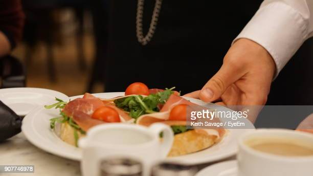 midsection of person serving food on table - keith savage stock-fotos und bilder