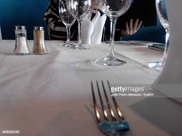 Midsection Of Person Sitting By Table With Salt And Pepper Shakers At Restaurant