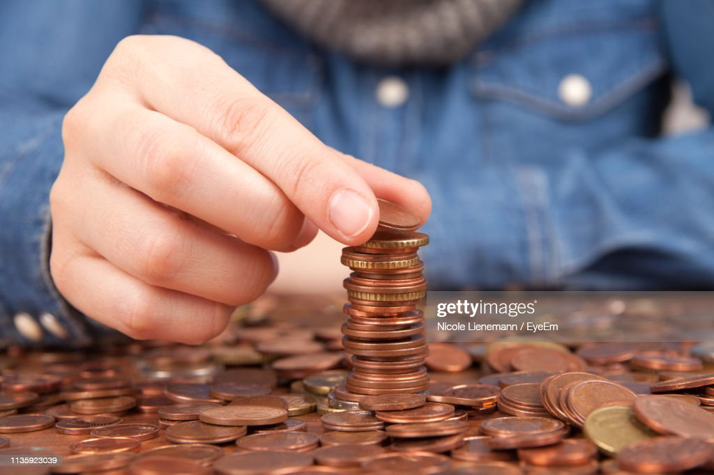 Midsection Of Person Stacking Coins At Home : Stock Photo