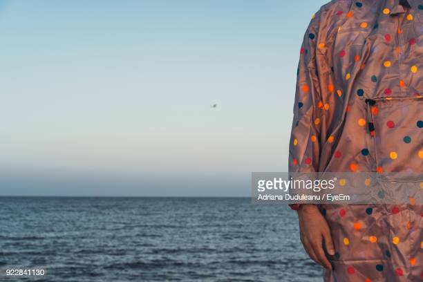 midsection of person standing against sea during sunset - adriana duduleanu stock photos and pictures
