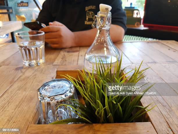 Midsection Of Person Using Smart Phone At Table