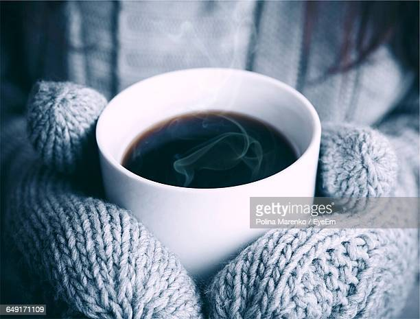 Midsection Of Person Wearing Gloves While Holding Coffee Cup