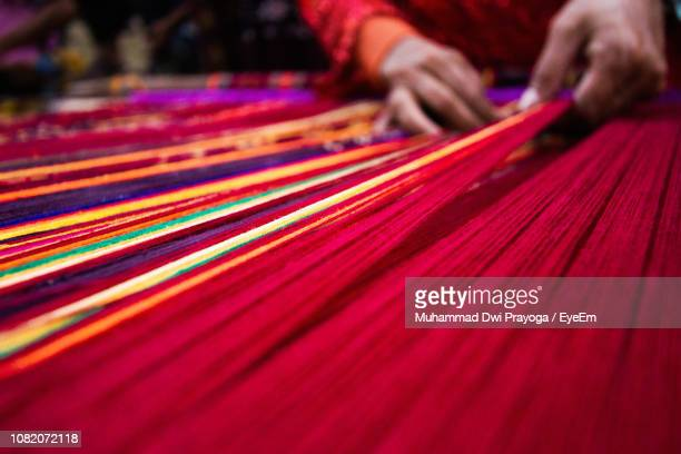 midsection of person weaving textile - woven stock photos and pictures