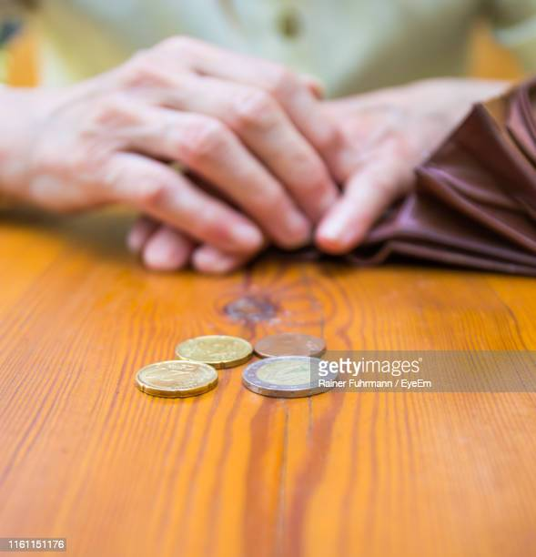 midsection of person with coins on table - ricchi e poveri foto e immagini stock