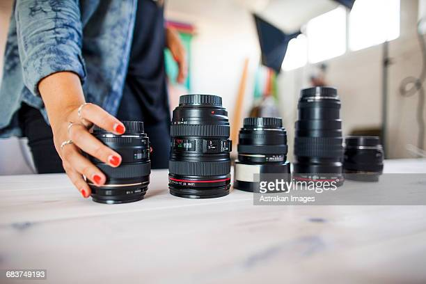 Midsection of photo assistant arranging various lenses on table in studio