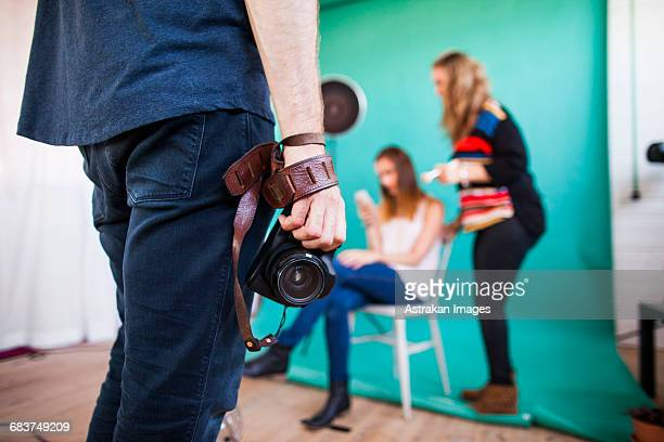 midsection of photographer holding digital camera while models getting dressed in background at studio - fotosession stock-fotos und bilder