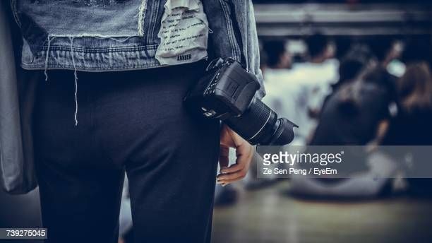 Midsection Of Photographer Standing With Camera Against People Sitting In Room