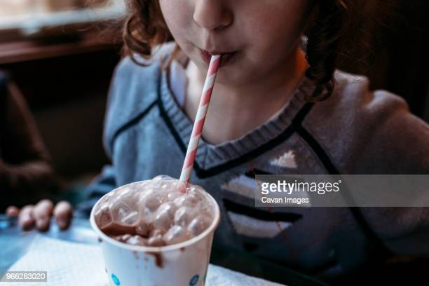 midsection of playful girl blowing bubbles in chocolate milk at home - milkshake imagens e fotografias de stock