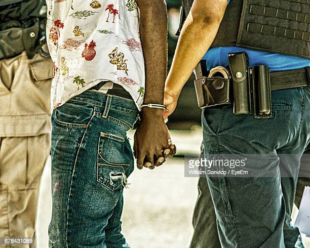 Midsection Of Police Arresting Thief