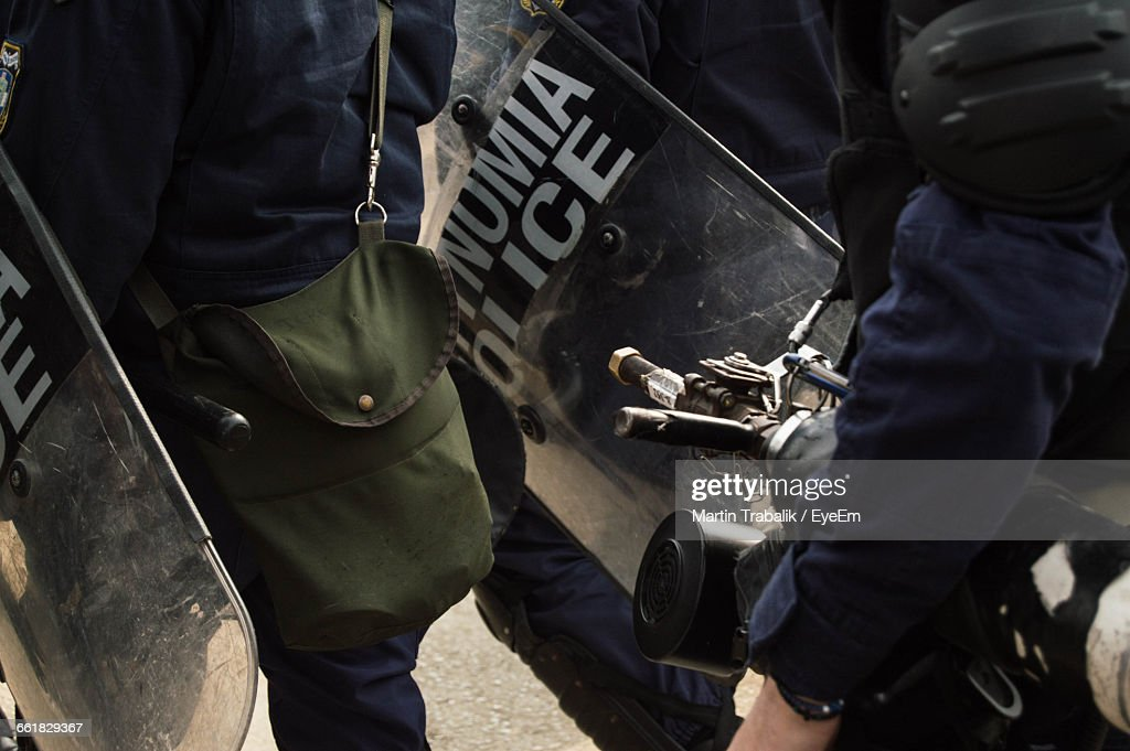 Midsection Of Police Force With Shield On Road : Stock Photo