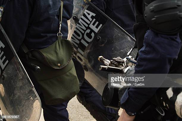 Midsection Of Police Force With Shield On Road