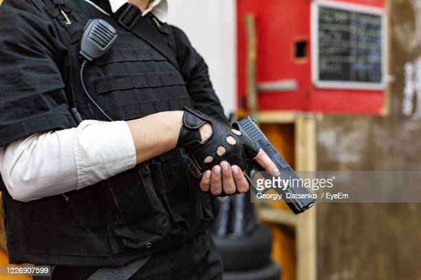 midsection of police holding gun - gun stock pictures, royalty-free photos & images
