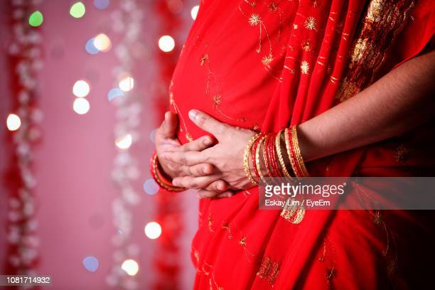 midsection of pregnant woman in red sari during diwali - sari stock pictures, royalty-free photos & images