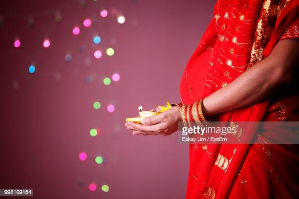 midsection of pregnant woman touching stomach - bangle stock pictures, royalty-free photos & images