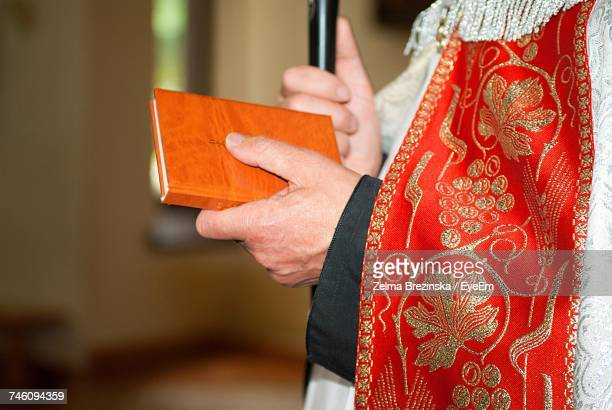 midsection of priest holding bible in church - catholicism stock pictures, royalty-free photos & images