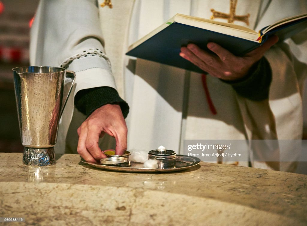 Midsection Of Priest Holding Book By Plate : Stockfoto