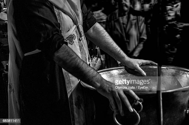 midsection of priest standing by container during baptism at church - christening gown stock pictures, royalty-free photos & images