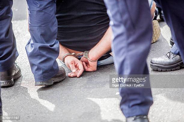 midsection of prisoner sitting on street surrounded with police force - arrest stock pictures, royalty-free photos & images