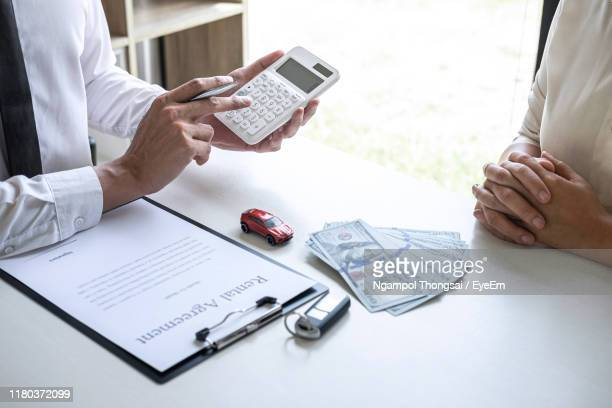 midsection of real estate agent showing calculation to customer while sitting by table at office - car insurance stock pictures, royalty-free photos & images
