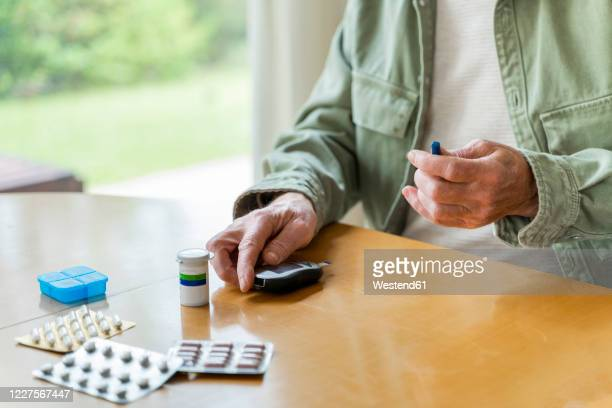 midsection of retired diabetic senior man examining himself while sitting at table - glucose stock pictures, royalty-free photos & images