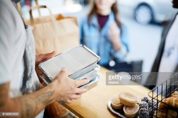 midsection of salesman holding takeaway packaged food for customers at concession stand - box container stock pictures, royalty-free photos & images