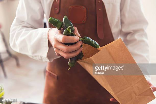Midsection of salesman putting green chili peppers in paper bag at grocery store