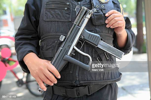 midsection of security officer holding gun on street - weapon stock pictures, royalty-free photos & images