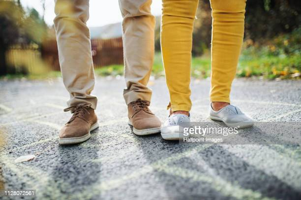 a midsection of senior couple standing on a road outdoors, on hopscotch. - old man feet stock pictures, royalty-free photos & images