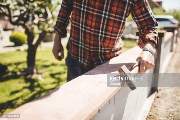 Midsection of senior man checking surrounding wall at yard