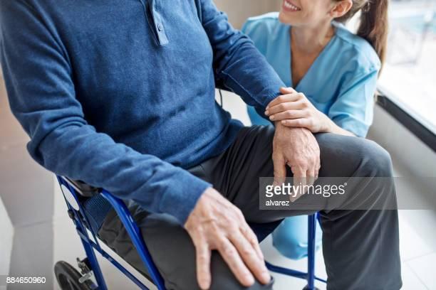 Abdomen d'homme senior sur fauteuil roulant par l'infirmière