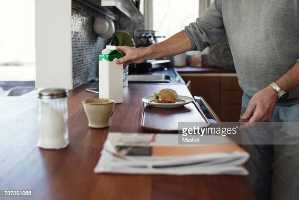 midsection of senior man preparing breakfast at kitchen counter - milk carton - fotografias e filmes do acervo