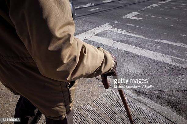 midsection of senior man standing with walking cane on sidewalk - walking cane stock photos and pictures