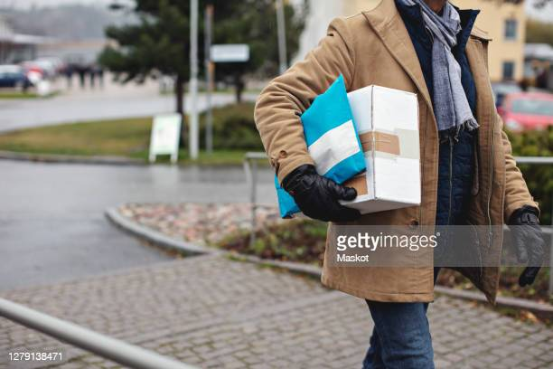 midsection of senior man with package walking by sidewalk during winter - human body part stock pictures, royalty-free photos & images