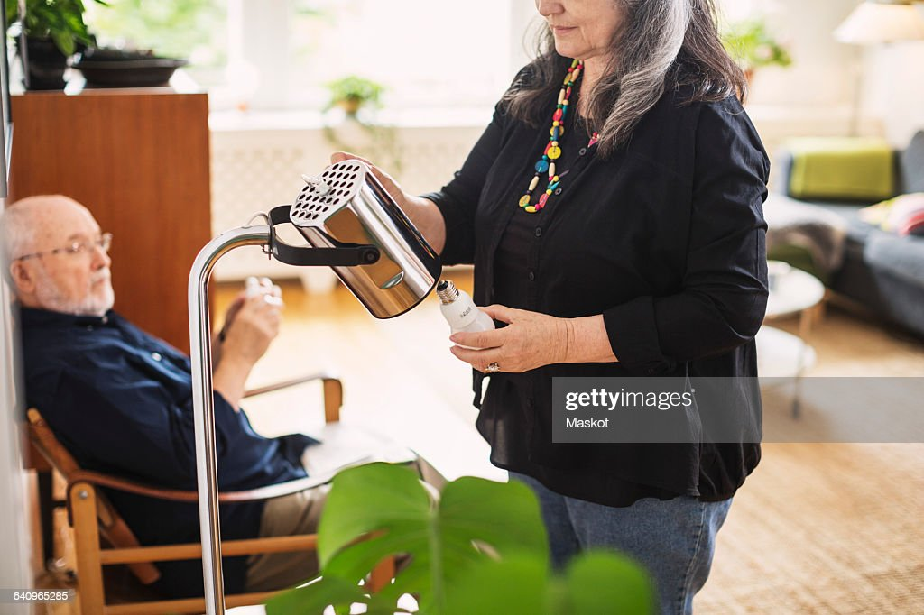 Midsection of senior woman changing bulb at home : Stock Photo