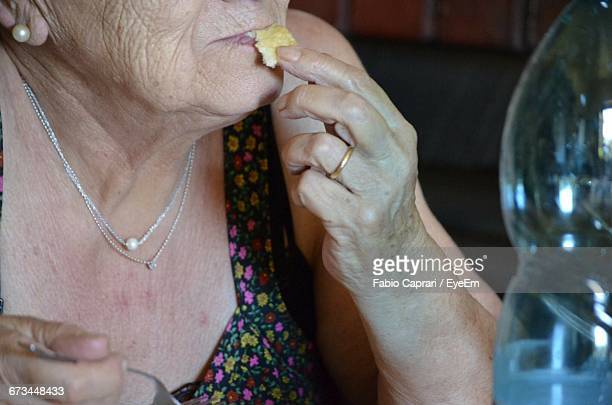 midsection of senior woman eating plum at home - pearl earring stock pictures, royalty-free photos & images