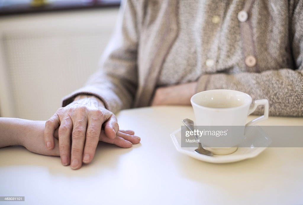 Midsection of senior woman lays her hand on another at home : Stock Photo