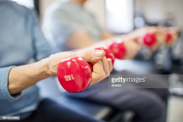 Midsection of senior woman lifting dumbbells