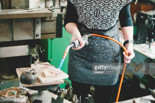 Midsection of senior woman using blowtorch for metalworking in jewelry workshop
