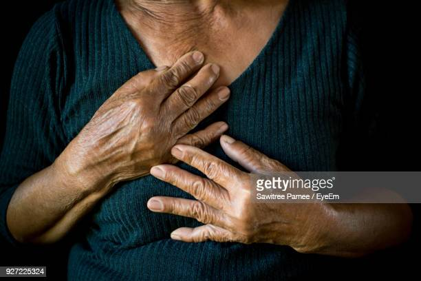 Midsection Of Senior Woman With Hands On Chest