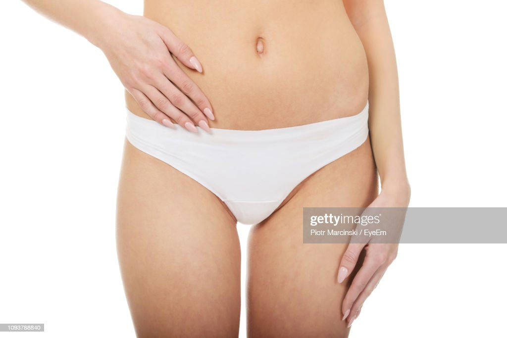 Midsection Of Sensuous Woman In White Panty Standing Against White Background : Foto de stock